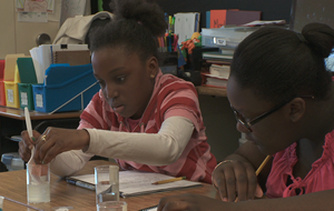 Photograph of two girls measuring the volume of a cube using water displacement.
